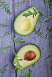 Avocado and arugula. On the wooden table Stock Photos