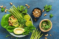 Avocado, asparagus, micro greens, lime, mint,basil, lettuce and cashew nuts. Detox bowl buddha. Blue rustic background, top view. stock image