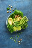 Avocado, asparagus, micro greens, lime, mint, lettuce and cashew nuts. Detox bowl buddha. Blue rustic background, top view. Clean, stock image