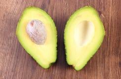 Avocado auf hölzernem Hintergrund, Bestandteil der Avocadopaste oder des Guacamolen, gesundes Lebensmittel und Nahrung Lizenzfreie Stockbilder