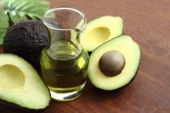 Avocado and avocado oil. Three fresh avocado and avocado oil on wood background stock photo