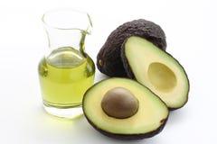 Avocado and avocado oil. Two fresh avocado and avocado oil on white background stock image
