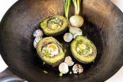 Avocado baked with quail eggs, fresh onion royalty free stock image