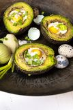 Avocado baked with quail eggs, fresh onion stock images