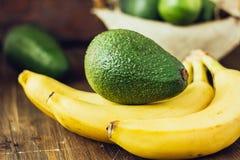 Avocado and banana over brown wooden background. Stock Photos