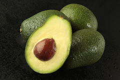 Avocado on black background. Group of avocado with half on black background Stock Images