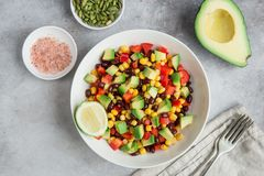 Avocado, black bean, corn and bell pepper salad in white bowl. Top view stock image