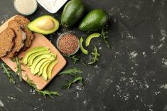Avocado, boter, brood ingrediënten voor het maken van avocadosandwiches Op een donkere achtergrond Mening van hierboven Met ruimt stock foto's