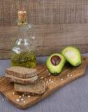 Avocado, Brot, Olivenöl auf einem hölzernen Brett Lizenzfreie Stockfotografie