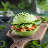 Avocado burger with salted salmon and fresh vegetables. Royalty Free Stock Photo