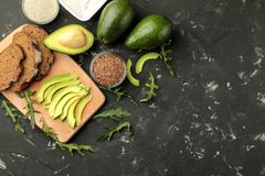 Avocado, butter, bread. ingredients for making avocado sandwiches. On a dark background. view from above. with space for text stock photos