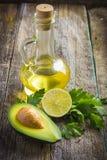 Avocado, calce, prezzemolo e olio d'oliva organici freschi su vecchio legno Fotografie Stock