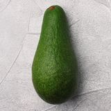 Avocado on cement background. whole avocado top view stock image