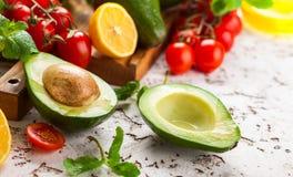 Avocado, cherry tomatoes, citrus and fresh herbs stock photo