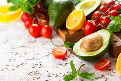 Avocado, cherry tomatoes, citrus and fresh herbs stock images