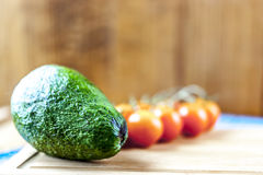 Avocado and cherry tomatoes on wooden background. With blue mat Royalty Free Stock Photos