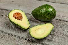 Avocado cięcie w połówce z całą zieloną bonkretą w tle na rusti obraz royalty free