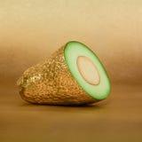 Avocado cięcie z złotą łupą na złocistym tle Fotografia Stock