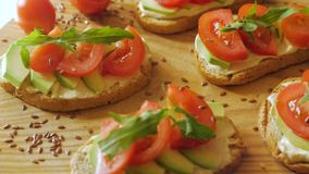 Avocado close up on the kitchen. Fresh toasts with avocado and tomatoes on wooden table stock video footage
