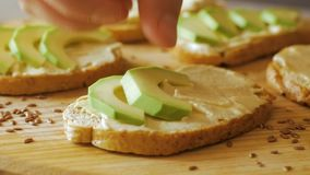 Avocado close up on the kitchen. Fresh toasts with avocado on wooden table stock footage