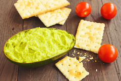 Avocado cream,biscuits and small tomatoes Stock Photos
