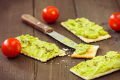Avocado cream,biscuits and small tomatoes Stock Images