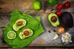 Avocado cream or guacamole on baguette canapes and ingredients l Stock Images