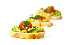 Avocado cream or guacamole and tomatoes on baguette canapes fre Royalty Free Stock Photo