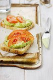Avocado cream with toasts and tomatoes. On a rustic surface Royalty Free Stock Image
