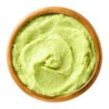 Avocado cream in wooden bowl over white Stock Image