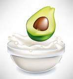 Avocado and creamy milk splash in bowl Royalty Free Stock Photos