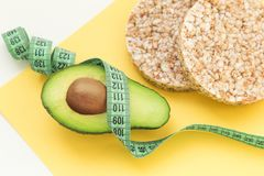 Free Avocado, Crispbread And Measuring Tape. Weight Loss And Proper Nutrition Royalty Free Stock Photography - 139199547