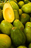 Avocado crop and half advocado cut. Avocado crop and half delicious ripe avocado cut in street market Stock Images