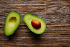 Avocado cut on aged wood table board Stock Images