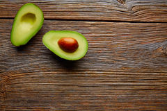 Avocado cut on aged wood table board Royalty Free Stock Image