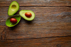 Avocado cut on aged wood table board Royalty Free Stock Photos