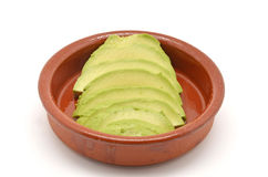 Avocado cut into clay bowl Stock Photo