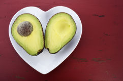 Avocado cut in half on heart shape plate Stock Photography