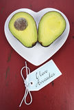 Avocado cut in half on heart shape plate. On dark red vintage rustic wood table, with I Love Avocados text sign, vertical stock photo