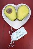 Avocado cut in half on heart shape plate Stock Photo