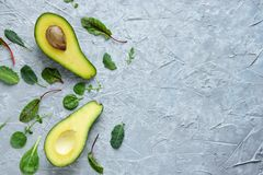 Avocado cut in half lies on a gray concrete background surrounded by nuts and green salad leaves ,snack Keto diet.  royalty free stock photos