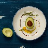 Avocado cut in two half parts with thyme and cedar nuts. Avocado cut in two half parts decorated with thyme, yellow sauce and cedar nuts lying on flat round Royalty Free Stock Photography