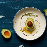 Avocado cut in two half parts with thyme and cedar nuts. Avocado cut in two half parts decorated with thyme, yellow sauce and cedar nuts lying on flat round Stock Image