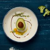 Avocado cut in two half parts with thyme and cedar nuts. Avocado cut in two half parts decorated with thyme, yellow sauce and cedar nuts lying on flat round Stock Photo