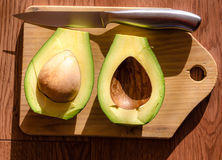 Avocado on cutting board with a knife. Royalty Free Stock Photo