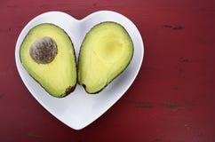 Avocado in de helft op de plaat die van de hartvorm wordt gesneden stock fotografie