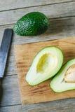 Avocado in de helft op houten lijst wordt gesneden die Royalty-vrije Stock Afbeelding