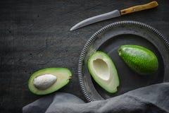 Avocado in de metaalplaat op de donkere gekraste mening van de lijstbovenkant Royalty-vrije Stock Afbeeldingen