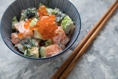 Avocado di color salmone crudo Tartaro con aneto ed il caviale di Keta in ciotola della porcellana con i bastoncini di legno fotografia stock libera da diritti