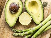 Avocado, die ein lächelndes Gesicht mit Spargel und Zitrone macht Lizenzfreie Stockbilder